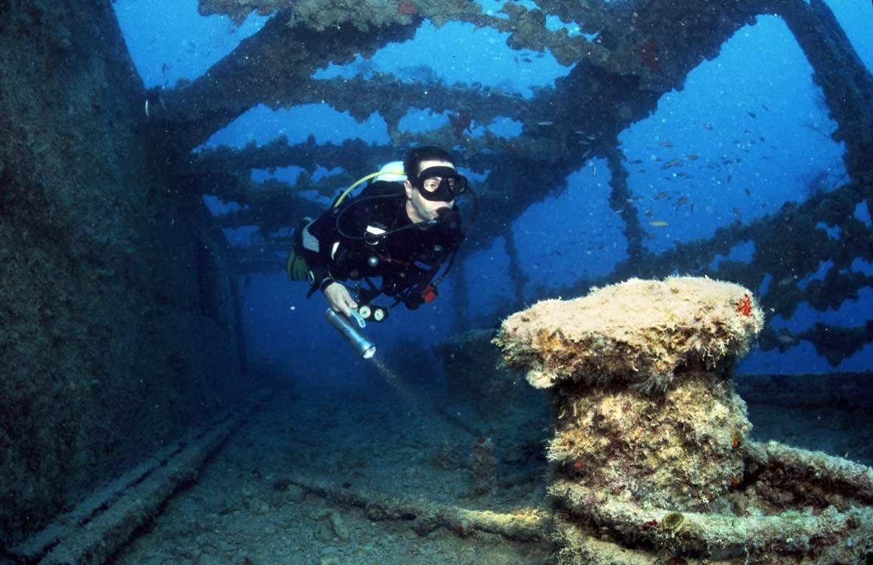 buceador nadando en el interior de un barco hundido